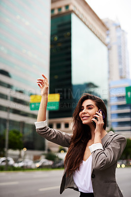 Buy stock photo Cropped shot of an attractive young businesswoman hailing for a taxi while taking a phonecall in the city during the day