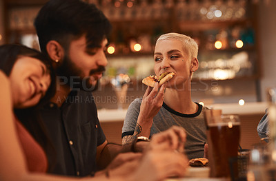 Buy stock photo Shot of a young woman having pizza with her friends at a restaurant