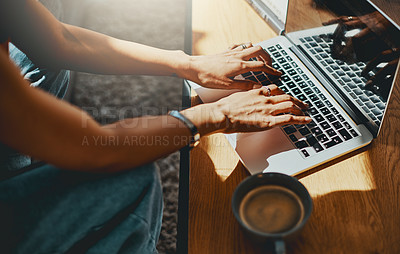 Buy stock photo Cropped shot of a woman using a laptop on the sofa at home