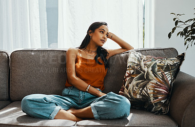 Buy stock photo Shot of a young woman looking thoughtful while relaxing on the sofa at home