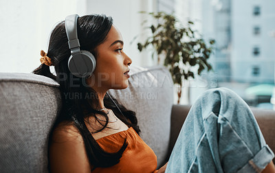 Buy stock photo Shot of a young woman using headphones while relaxing on the sofa at home