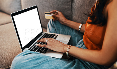 Buy stock photo Cropped shot of a woman using a laptop and credit card on the sofa at home