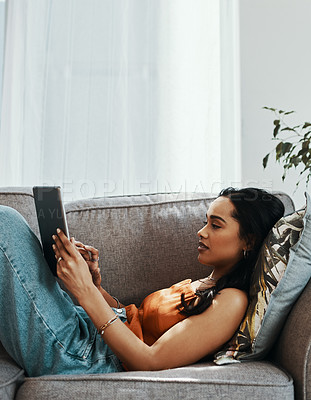 Buy stock photo Shot of a young woman using a digital tablet on the sofa at home