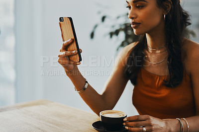 Buy stock photo Shot of a young woman using a smartphone and having coffee at home
