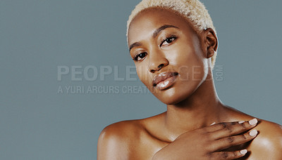 Buy stock photo Cropped shot of an attractive young woman standing alone with her hand on her shoulder against a gray studio background