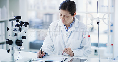 Buy stock photo Shot of a young scientist using a clipboard and digital tablet in a lab