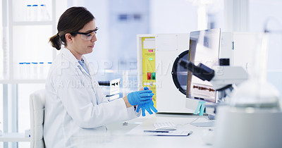 Buy stock photo Shot of a young scientist taking off her gloves while working on a computer in a lab