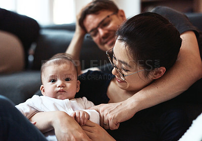 Buy stock photo Shot of a happy young couple bonding and spending time with their infant daughter at home