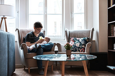 Buy stock photo Shot of a happy father feeding and spending time with his infant daughter at home