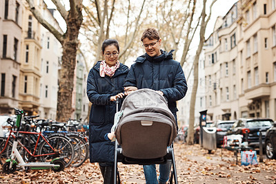 Buy stock photo Shot of a happy young couple pushing their infant daughter in her pram on a day spent together outdoors