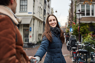 Buy stock photo Shot of a woman pulling her boyfriend by the hand while exploring a foreign city