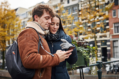 Buy stock photo Shot of a man showing his girlfriend something on his cellphone while exploring a foreign city