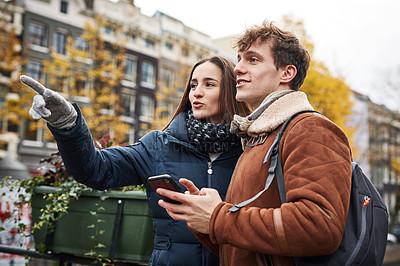Buy stock photo Shot of a couple using a cellphone while exploring a foreign city