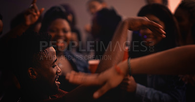 Buy stock photo Cropped shot of a handsome young man dancing while partying with his friends in a nightclub