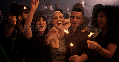 Buy stock photo Cropped shot of a group of young friends holding up sparklers while partying in a nightclub