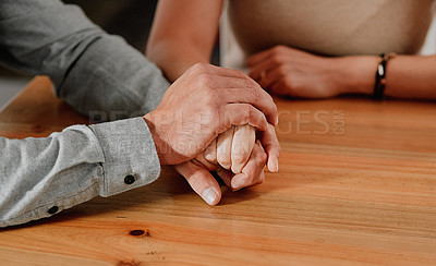 Buy stock photo Cropped shot of an unrecognizable couple holding hands on a wooden table