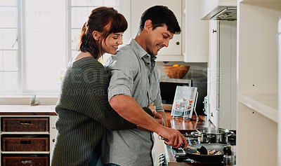 Buy stock photo Shot of a man cooking while being embraced by his wife at home