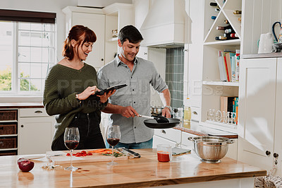 Buy stock photo Shot of a couple using a digital tablet while cooking at home