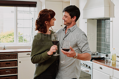Buy stock photo Cropped shot of an affectionate couple enjoying a glass of wine at home