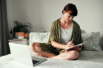 Buy stock photo Full length shot of an attractive young woman writing notes in her diary while relaxing in her bedroom at home