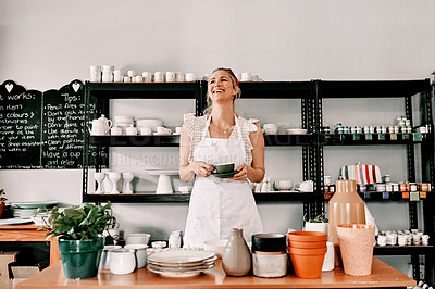 Buy stock photo Cropped shot of an attractive mature woman standing alone and holding a cup of coffee in her pottery workshop