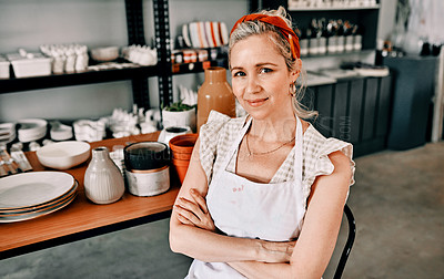 Buy stock photo Cropped portrait of an attractive mature woman sitting with her arms folded in her pottery workshop