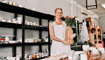 Buy stock photo Cropped portrait of an attractive mature woman standing alone and holding a handmade vase in her pottery workshop