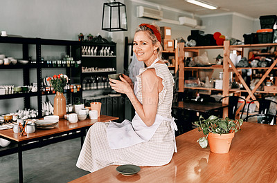 Buy stock photo Cropped portrait of an attractive mature woman sitting alone and holding a cup of coffee in her pottery workshop