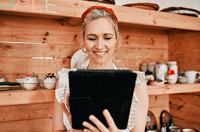 Buy stock photo Cropped shot of an attractive mature woman standing alone and using a tablet in her pottery workshop