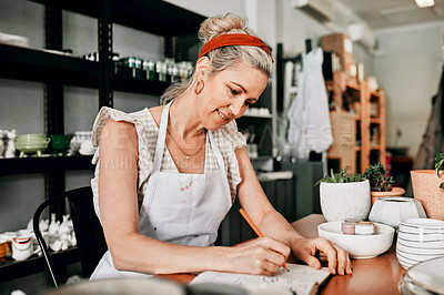 Buy stock photo Cropped shot of an attractive mature woman sitting alone in her pottery workshop and sketching in a notebook