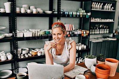 Buy stock photo Cropped portrait of an attractive mature woman sitting alone and using her laptop in her pottery workshop