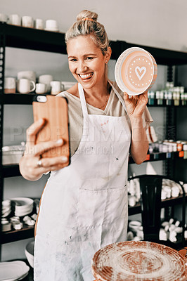 Buy stock photo Cropped shot of an attractive mature woman using her cellphone to take a selfie with her pottery in her studio