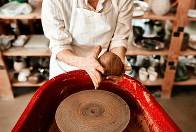 Buy stock photo Cropped shot of an unrecognizable woman molding clay on a pottery wheel