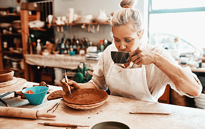 Buy stock photo Shot of a female artisan having coffee while working in her pottery workshop