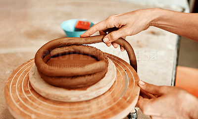 Buy stock photo Cropped shot of a woman shaping a clay pot in her workshop