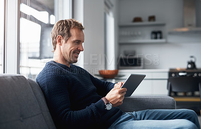 Buy stock photo Cropped shot of a handsome young man sitting alone on the sofa at home and using a tablet