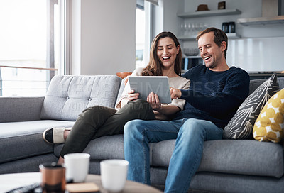 Buy stock photo Cropped shot of a happy young couple sitting on the sofa together and using a tablet at home