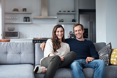 Buy stock photo Cropped portrait of an affectionate young couple sitting together on their sofa at home during a day off