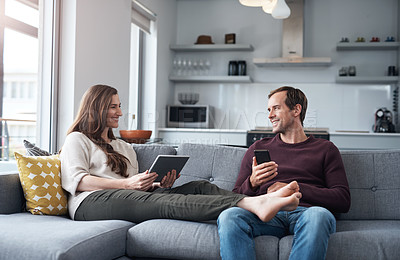 Buy stock photo Cropped shot of an affectionate young couple sitting on their sofa at home together and using technology