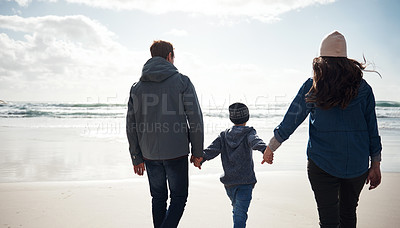 Buy stock photo Cropped shot of an unrecognizable family holding hands and walking along the beach together during a day out
