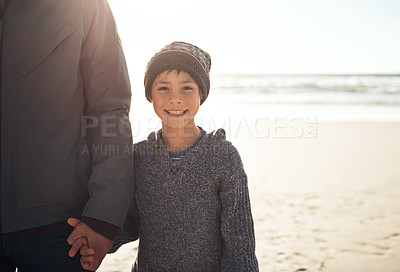 Buy stock photo Cropped portrait of a happy young boy standing and holding his father's hand during a day out on the beach