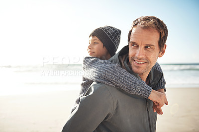 Buy stock photo Cropped shot a handsome young man giving his son a piggy back while bonding together on the beach