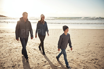 Buy stock photo Full length shot of a happy young family walking along the beach together during a day out