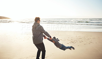 Buy stock photo Cropped shot of a handsome young man feeling playful while enjoying a day out on the beach with his son