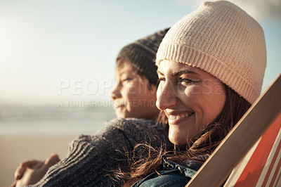 Buy stock photo Cropped shot of an attractive young woman sitting and hugging her son during an enjoyable day out on the beach