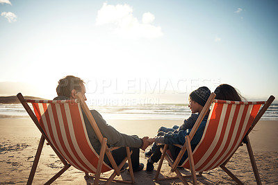 Buy stock photo Full length shot of a happy young family sitting on sun loungers during an enjoyable day out on the beach