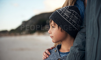 Buy stock photo Cropped shot of a young boy standing with his parent and enjoying a sunset on the beach