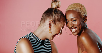 Buy stock photo Studio shot of two beautiful young women looking cheerful while posing against a pink background