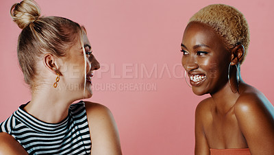 Buy stock photo Studio shot of two beautiful young women smiling at each other against a pink background