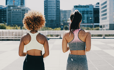 Buy stock photo Rearview shot of two unrecognizable sportswomen jogging together outdoors in the city
